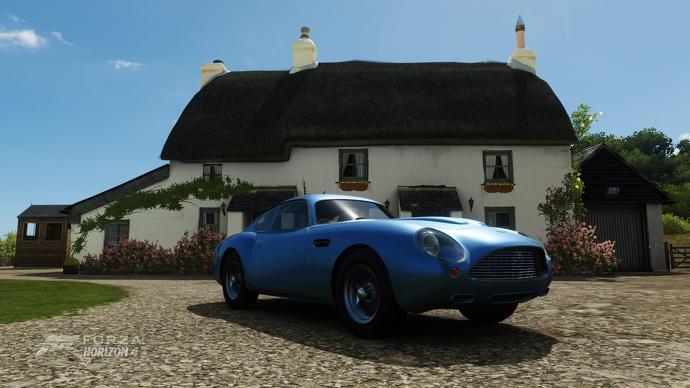 Un coche clásico frente a una casa de campo en Forza Horizon 4